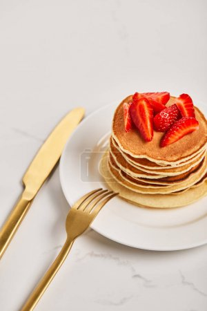 Photo for Golden fork on plate with pancakes and strawberries and knife near plate - Royalty Free Image