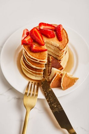 Photo for Plate with pancakes and slice of pancakes with strawberries near golden cutlery - Royalty Free Image