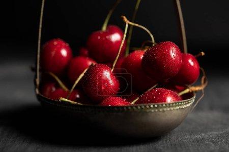 Photo pour Foyer sélectif de cerises rouges humides délicieuses dans le panier en métal sur table sombre en bois isolé sur noir - image libre de droit