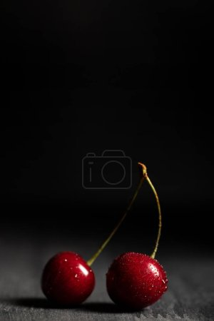 Photo for Close up view of red delicious cherries with water drops on wooden table isolated on black - Royalty Free Image