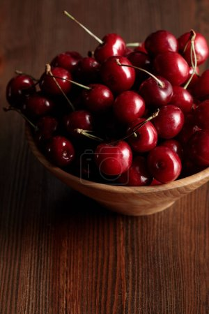 wooden bowl with red ripe cherries on wooden brown table