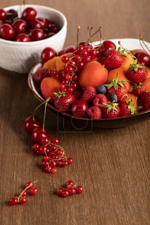 Photo for Selective focus of red cherries in white bowl and mixed berries on plate on wooden table - Royalty Free Image