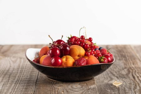 Photo for Plate with mixed delicious ripe berries on wooden table isolated on white - Royalty Free Image