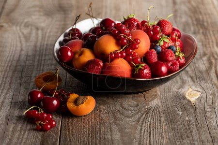 Photo for Plate with mixed delicious ripe berries on wooden table - Royalty Free Image