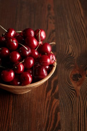 Photo for Red delicious cherries in wooden bowl on wooden brown table - Royalty Free Image