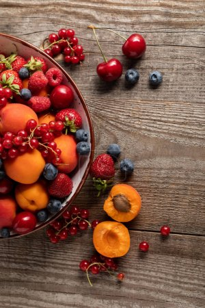 Photo for Top view of ripe seasonal berries and apricots on plate on wooden table - Royalty Free Image