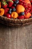 """Постер, картина, фотообои """"крупным планом зрения спелых сезонных ягод и абрикосов в плетеной корзине на деревянном столе"""""""