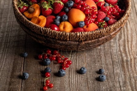 Photo for Close up view of ripe seasonal berries and apricots in wicker basket on wooden table with copy space - Royalty Free Image