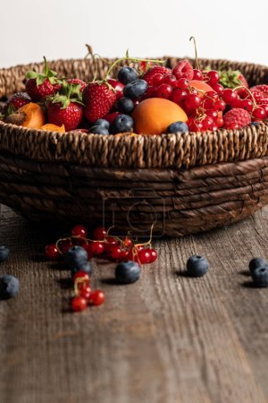 Photo for Close up view of ripe seasonal berries and apricots in wicker basket on wooden table isolated on white - Royalty Free Image