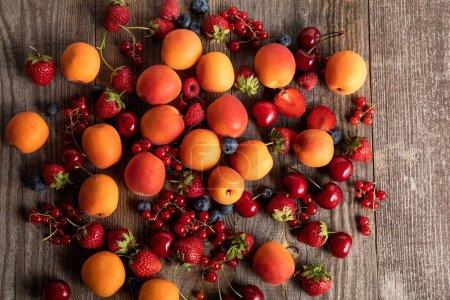 Foto de Vista superior de deliciosas bayas frescas maduras y albaricoques esparcidos en la mesa de madera - Imagen libre de derechos