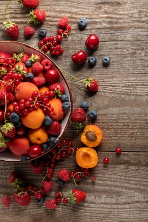 Photo for Top view of ripe delicious fresh berries and apricots in plate and around on wooden table - Royalty Free Image