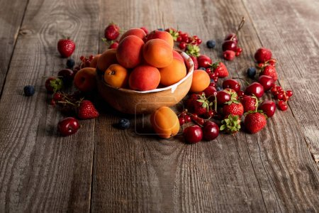 Photo for Ripe delicious seasonal berries scattered around bowl with apricots on wooden table - Royalty Free Image