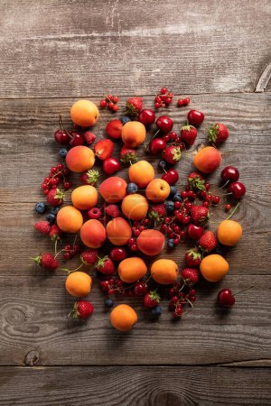 Photo for Top view of ripe delicious fresh berries and tasty apricots on wooden table - Royalty Free Image