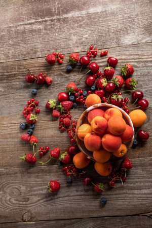 Photo for Top view of ripe delicious seasonal berries scattered around bowl with apricots on wooden table - Royalty Free Image