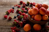 """Постер, картина, фотообои """"ripe delicious seasonal berries scattered around bowl with fresh apricots on wooden table """""""