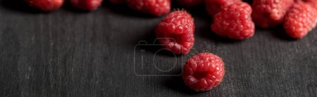 Photo for Selective focus of delicious ripe raspberries scattered on wooden table, panoramic shot - Royalty Free Image