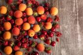 """Постер, картина, фотообои """"верхний вид спелых вкусных сезонных ягод, разбросанных со свежими абрикосами на деревянном столе"""""""