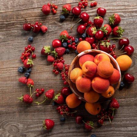 Foto de Vista superior de las deliciosas bayas de temporada maduras esparcidas alrededor de un tazón con albaricoques frescos en una mesa de madera - Imagen libre de derechos