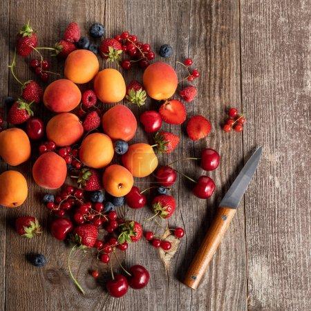 Photo pour Vue de dessus de baies mûres délicieuses de saison parsemées d'abricots frais sur une table en bois près d'un couteau - image libre de droit