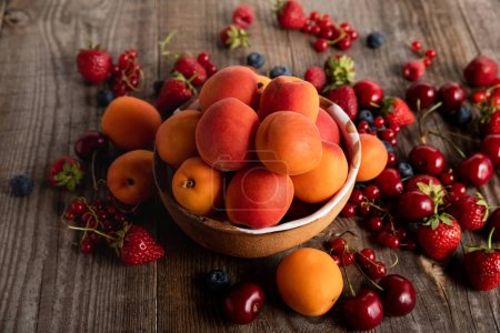 Photo for Ripe seasonal berries scattered around bowl with fresh apricots on wooden table - Royalty Free Image
