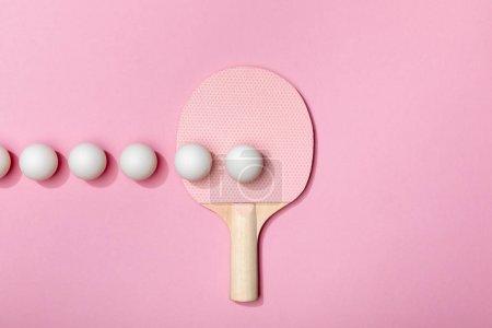Photo pour Plat s'est couché avec les boules blanches de ping-pong et la raquette sur le fond rose - image libre de droit