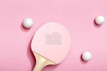 top view of white table tennis balls scattered near pink racket on pink background