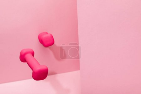 Photo for Pink bright dumbbells flying in air on pink background with copy space - Royalty Free Image