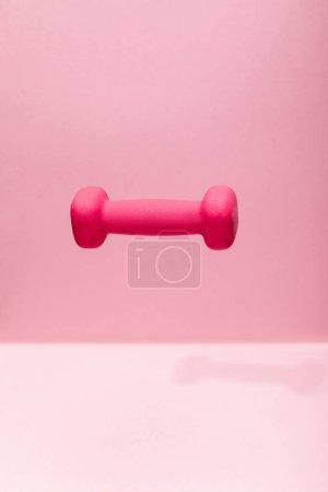 Photo pour Haltère lumineux rose lévitant dans l'air sur fond rose - image libre de droit