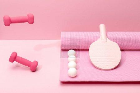 Photo pour Haltères roses lévitation dans l'air près des boules blanches de ping-pong et de la raquette sur le tapis de forme physique sur le fond rose - image libre de droit
