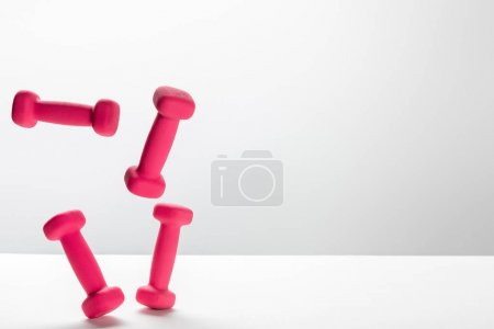 Photo for Pink bright dumbbells flying in air on white background with copy space - Royalty Free Image