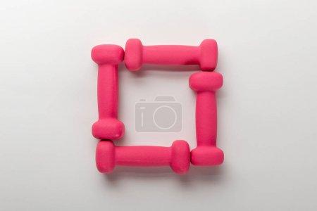 Photo pour Vue de dessus du cadre avec haltères roses sur fond blanc - image libre de droit