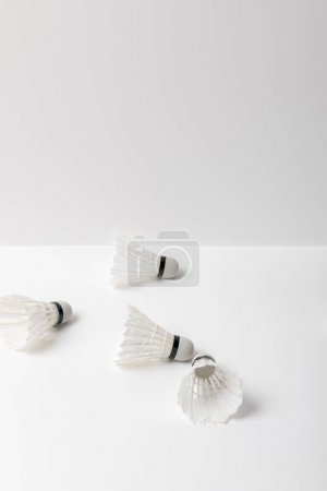 white badminton shuttlecocks scattered on white background with copy space