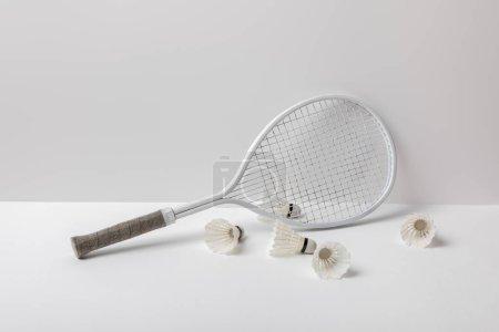 Photo pour Navettes de badminton blanc près de raquette blanche sur fond blanc - image libre de droit