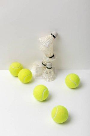 weiße Federbälle und knallgelbe Tennisbälle auf weißem Hintergrund