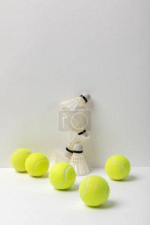 Photo pour White badminton shuttlecocks and yellow tennis balls on white background - image libre de droit