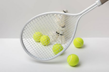 Photo for White badminton shuttlecocks and bright yellow tennis balls near racket on white background - Royalty Free Image
