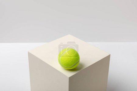Photo pour Balle de tennis jaune vif sur cube sur fond blanc - image libre de droit