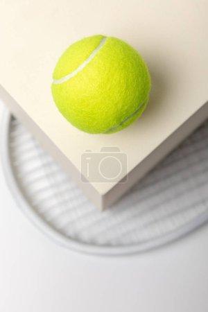 Foto de Enfoque selectivo de la pelota de tenis amarillo brillante en cubo y raqueta sobre fondo blanco - Imagen libre de derechos