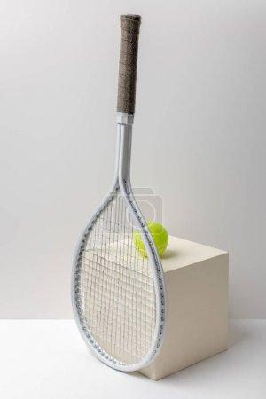 Photo pour Raquette de tennis et balle de tennis jaune vif sur cube sur fond blanc - image libre de droit