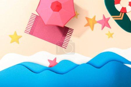 Photo pour Vue supérieure de plage de papier avec des étoiles de mer, une serviette, un parapluie et une planche de surf avec bouée de sauvetage sur le sable près de la mer - image libre de droit