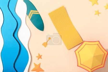 Photo pour Vue supérieure de la plage de papier avec le parapluie jaune et sur le sable près de l'océan, de la planche de surf et des étoiles de mer - image libre de droit
