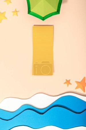 Photo pour Vue supérieure de la plage de papier avec la serviette jaune, le parapluie vert et les étoiles de mer sur le sable près de l'océan - image libre de droit