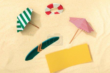 Photo pour Vue de dessus de la plage de papier avec bouée de sauvetage, parasols, planche de surf et serviette sur sable texturé - image libre de droit