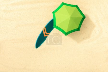 Photo pour Vue supérieure de la plage de papier avec le parapluie vert et la planche de surf sur le sable texturé - image libre de droit