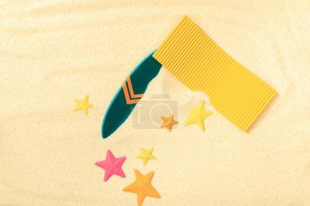 Photo pour Vue supérieure de la plage de papier avec la planche de surf verte, la serviette jaune et les étoiles de mer sur le sable texturé - image libre de droit