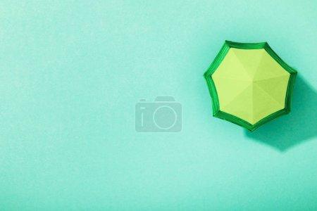 Photo pour Vue supérieure du parapluie de papier sur le fond turquoise - image libre de droit