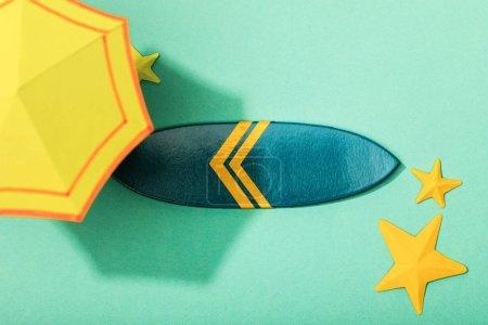 Photo pour Vue supérieure du parapluie jaune de papier près des étoiles de mer et de la planche de surf sur le fond turquoise - image libre de droit