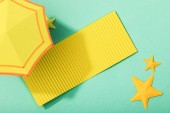 "Постер, картина, фотообои ""top view of paper cut yellow towel and umbrella near starfishes on turquoise background"""