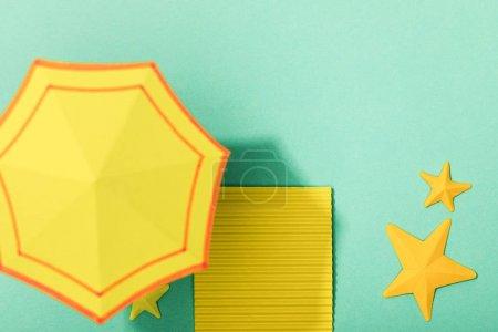 Photo pour Vue supérieure de la serviette et du parapluie jaunes de papier près des étoiles de mer sur le fond turquoise - image libre de droit