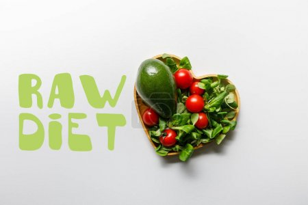 Photo for Top view of fresh green vegetables in heart shaped bowl on white background with raw diet lettering - Royalty Free Image